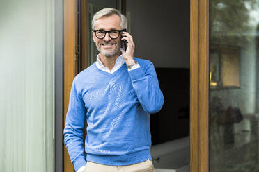 Smiling senior man with grey hair standing in front of his modern design home talking on the phone - SBOF02126
