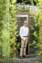Senior man with grey hair holding smartphone in front of his modern design home in bamboo garden - SBOF02135