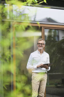 Smiling senior man with grey hair holding tablet in front of his modern design home in bamboo garden - SBOF02138
