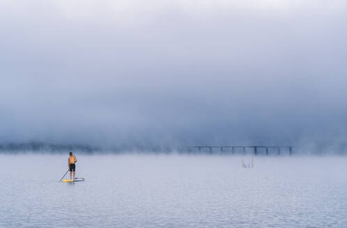 Man stand up paddle surfing on a lake in the fog - DGOF00456