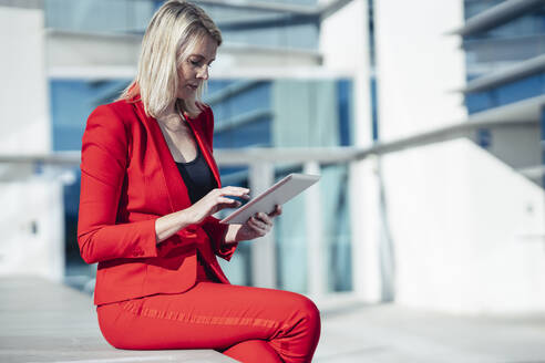 Blond businesswoman wearing red suit and using digital tablet at an office building - JSMF01441