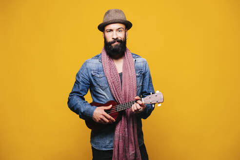 Portrait of a bearded young man in studio holding ukulele - DGOF00468