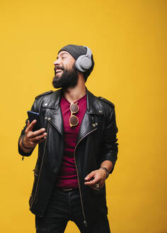 Portrait of a happy young man in studio with smartphone and headphones - DGOF00480