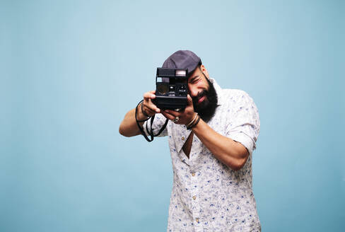 Bearded young man in studio taking picture with instant camera - DGOF00486