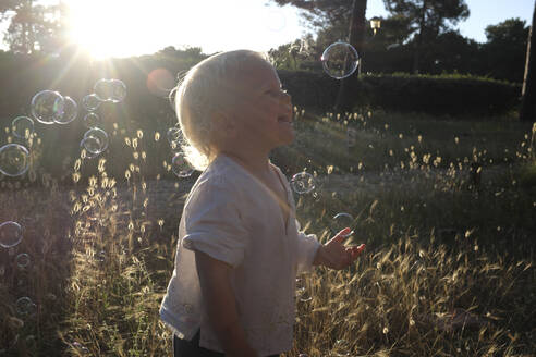 Happy little girl playing with soap bubbles in summer - GISF00546
