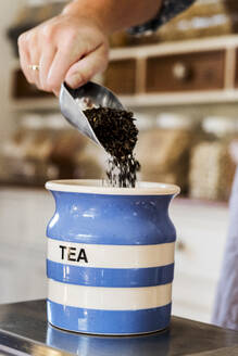 Close up of person standing in a kitchen, placing loose tea into striped blue ceramic jar. - MINF13877