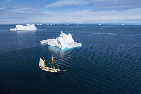 Ship sailing past majestic icebergs on sunny blue Atlantic Ocean Greenland - HOXF05179