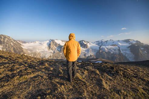 Rear view of hiker walking on mountain summit in yellow jacket. - CAVF75533