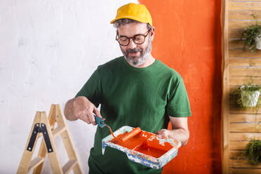 Smiling man holding paint tray with orange paint - RTBF01423