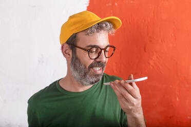 Portrait of man using smartphone in front of orange wall - RTBF01426