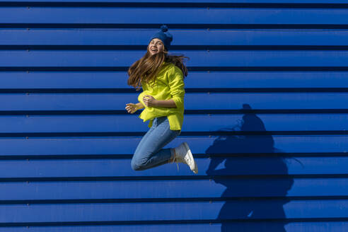 Laughing teenage girl jumping in the air in front of blue background - ERRF02696