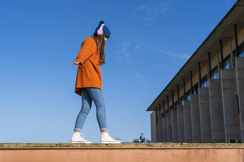 Teenage girl balancing on a wall against while listening music with headphones - ERRF02711