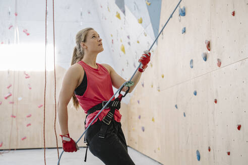 Woman with a rope securing partner on the wall in climbing gym - AHSF01962