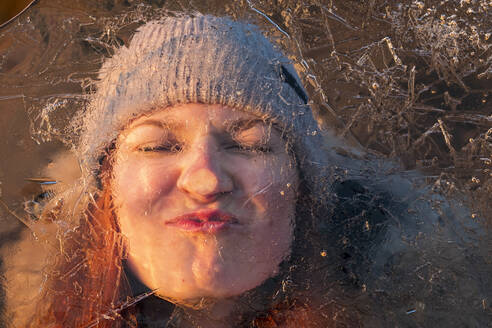 Portrait of teenage girl pulling funny face behind ice-covered surface - LBF02904