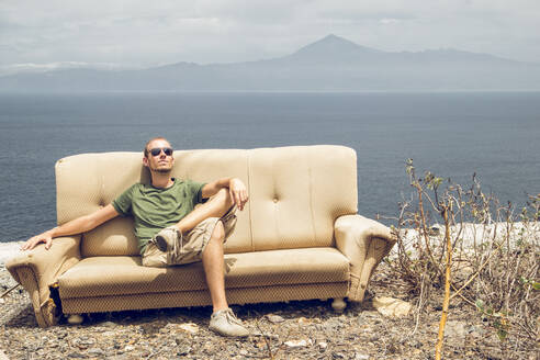 Young man relaxing on broken couch, enjoying the sun, La Gomera, Spain - MAMF01219