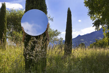 Woman hiding behing tree, holding mirror, reflecting the sky - PSTF00592