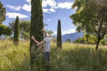 Woman standing in meadow, hugging cypresse - PSTF00595