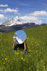 Woman sitting in meadow, hiding behind mirror, reflecting the mountains of Val Badia, Alto Adige, Italy - PSTF00601