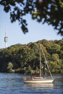 Germany, Brandenburg, Potsdam, Sailboat moored on Havel river with TV tower in background - ASCF01117