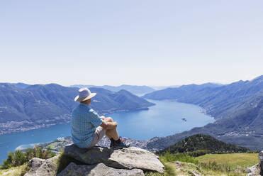 Hiker at Cimetta mountain top looking towards Lago Maggiore and Ascona, Locarno, Ticino, Switzerland - GWF06496