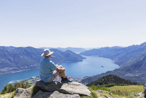 Hiker at Cimetta mountain top looking towards Lago Maggiore and Ascona, Locarno, Ticino, Switzerland - GWF06496