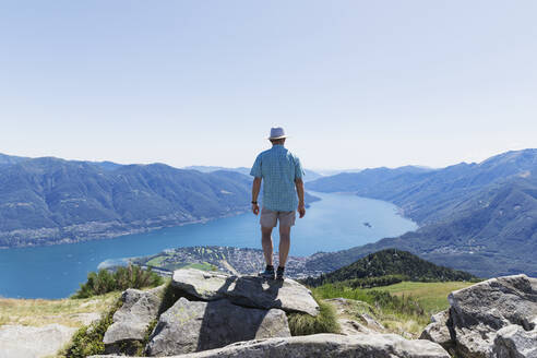 Hiker at Cimetta mountain top looking towards Lago Maggiore and Ascona, Locarno, Ticino, Switzerland - GWF06499