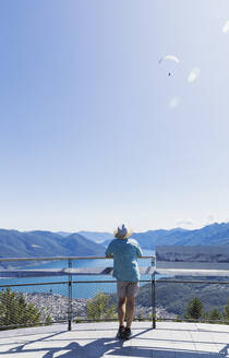 Hiker standing on viewing platform Cardada above Locarno looking towards Lago Maggiore, Ticino, Switzerland - GWF06502