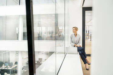 Blond businesswoman with laptop, sitting on windowsill in office building - PESF01849