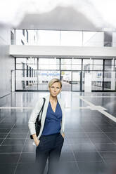 Successful businesswoman standing in entrance hall of office building, lokking at camera - PESF01861