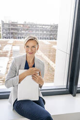 Blond businesswoman with laptop, sitting on windowsill in office building - PESF01864