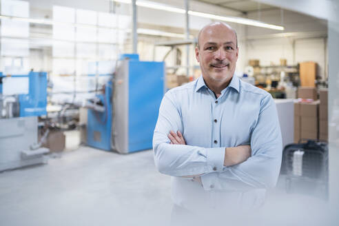 Portrait of a confident businessman in a factory - DIGF09308