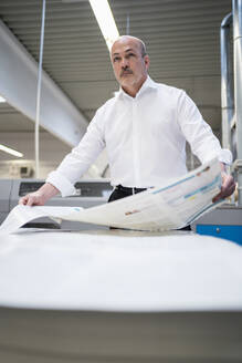 Businessman in a printing plant holding paper - DIGF09329