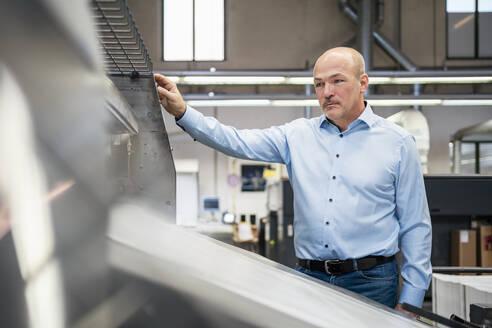 Businessman at a machine in a factory - DIGF09365