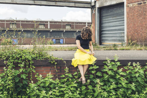 Woman sitting on a plant covered wall in an old industrial area - HBIF00054