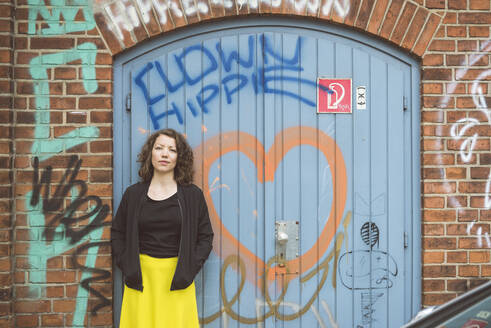 Portrait of brunette woman standing in front of a brick wall with an old gate and graffiti - HBIF00060