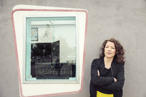 Portrait of brunette woman next to a window of a retro bistro - HBIF00066