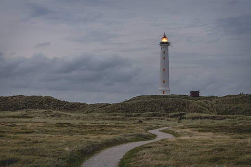 Denmark, Hvide Sande, Footpath toward coastal lighthouse at dusk - KEBF01463