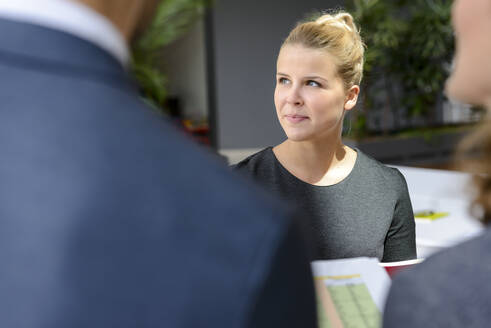 Young businesswoman talking to colleagues in a business meeting, portrait - BMOF00241