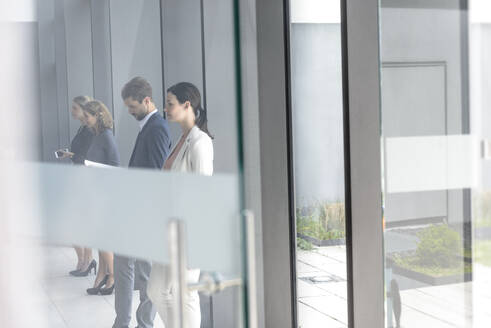 Business people waiting in office building, leaning on glass pane - BMOF00250