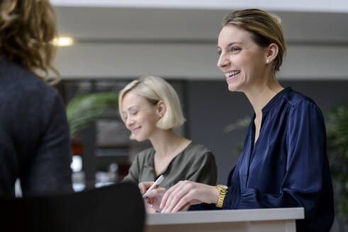 Attentive businesswomen sitting meeting, listening smiling - BMOF00259
