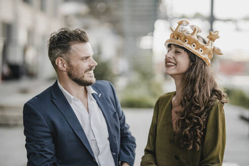 Smiling businessman looking at woman wearing a crown - KNSF07614