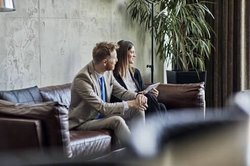 Businessman and businesswoman sitting on couch in hotel lobby during a meeting - ZEDF02977