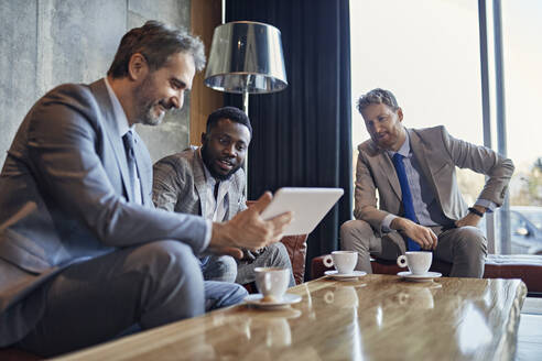 Three businessmen sitting in hotel lobby with tablet - ZEDF03037