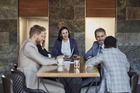Business people having a meeting in hotel lobby - ZEDF03043