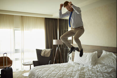 Excited businessman jumping on bed in hotel room - ZEDF03112