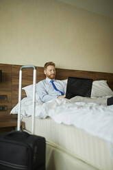 Businessman lying on bed in hotel room using laptop - ZEDF03115
