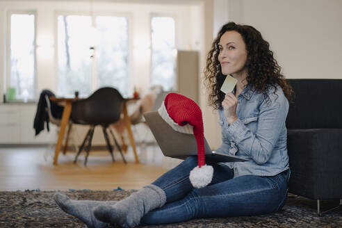 Woman with Santa hat shopping for presents online, using laptop - JOSEF00002