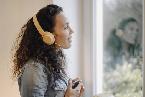 Woman listening music, wearing headphones, using smartphone - JOSEF00020