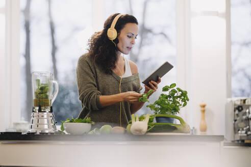 Fit woman standing in kitchen, preparing healthy smoothie, using online recipe - JOSEF00041