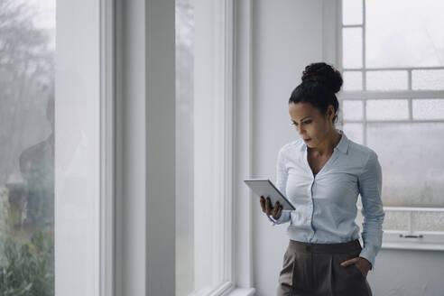 Successful businesswoman, standing by window, using digital tablet, reading - JOSEF00098